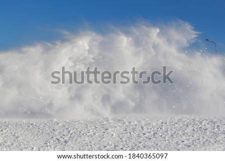 Vortexes of snow during the blizzard on blue sky background in the region of the far North. The theme of a natural disaster and the harsh polar climate. Typical picture of a northern winter.