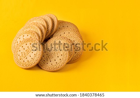 Many Marie biscuits  on bright yellow background. Modern cookies concept.  Royalty-Free Stock Photo #1840378465