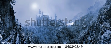 The famous Neuschwanstein Castle in the background of snowy mountains and hills in in the light of the sun through a snowstorm and blizzard. Germany, Europe Royalty-Free Stock Photo #1840393849