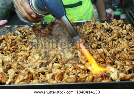 """Indonesian street food """"Cumi Bakar"""". Grilled squid. selective focus. grainy picture"""
