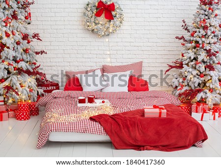 Cozy Decorated bedroom for Christmas holidays with tree and gifts. Spacious white light bedroom in a loft style with a decorated Christmas spruces, garland, bed with pillows. interior xmas bedroom   #1840417360