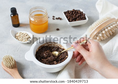 Homemade body scrub made with ground coffee, honey and oatmeal in a jar on gray concrete table. Self-care at home, eco homemade cosmetic for spa and skin care. Royalty-Free Stock Photo #1840439713