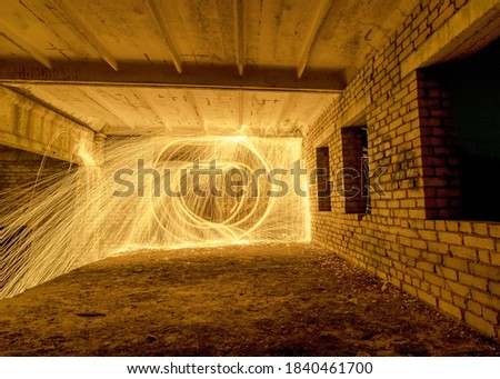 Picture playing fireworks, turning the line into a wave shape, sparks on the light, an amazing fire dance in an old white brick building and beautiful reflections, a light painting