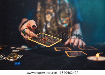 Astrology and esotericism. The female hand of the sorceress throws a Tarot card. Close up Royalty-Free Stock Photo #1840463422