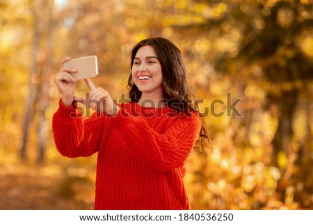 Pretty young lady taking picture of beautiful autumn nature on smartphone camera at park. Millennial female photographer making photos outside on bright fall day, copy space