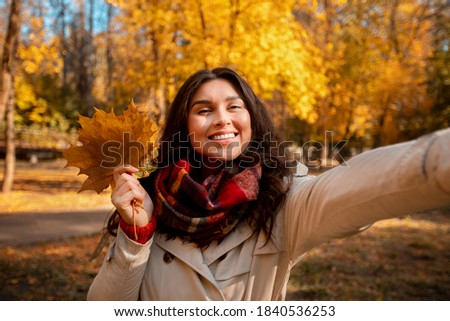 Beautiful young woman in fashionable fall clothes holding bouquet of autumn leaves and taking selfie at park. Pretty millennial lady making photo of herself during her walk outside