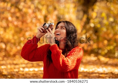 Professional female photographer taking photos with retro camera outside on sunny autumn day. Happy young woman making pictures of fall nature during her walk at park