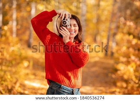 Portrait of positive female photographer with retro camera taking photos of yellow autumn at park. Pretty millennial woman photographing colorful nature on sunny fall day