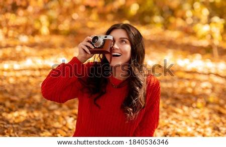 Smiling young woman in bright red sweater making pictures with retro camera at park on sunny fall day. Female photo artist photographing fading nature in autumn, outdoors. Panorama