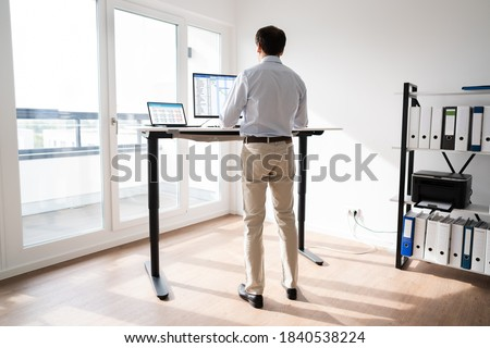 Man Working On Computer At Standing Desk In Home Office  Royalty-Free Stock Photo #1840538224