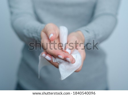 Woman cleans hands wet antibacterial wipe on gray background Royalty-Free Stock Photo #1840540096