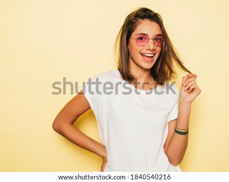 Young beautiful woman looking at camera. In casual summer white T-shirt and jeans shorts in round sunglasses. Positive female shows facial emotions. Funny model isolated on yellow  Royalty-Free Stock Photo #1840540216