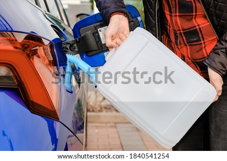 Woman filling a diesel engine fluid from canister into the tank of blue car. Diesel exhaust fluid for reduction of air pollution.  Royalty-Free Stock Photo #1840541254