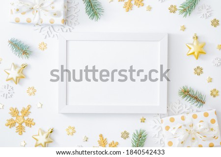 Mockup white frame with fir branches, christmas baubles decoration, gift box and snowflakes on a white background