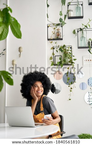 Young happy stylish African American gen z hipster teenage girl student with Afro hair laughing, looking through window, sitting at table in modern cozy cafe interior, holding phone, using laptop. Royalty-Free Stock Photo #1840561810