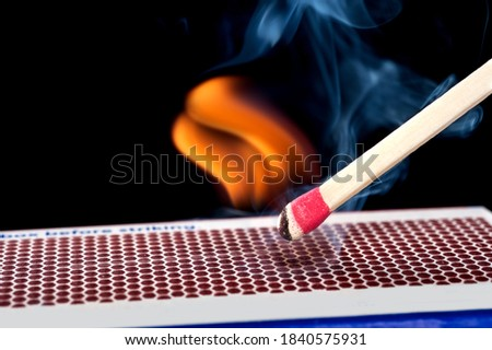 A matchstick lights after it is struck agains the flint surface of a match box.  Everything is real, no flame filters. Royalty-Free Stock Photo #1840575931