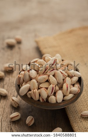 Pistachios in a bowl on wooden surface pistachios in a metal bowl on jute cloth, pile of pistachios, roasted pistachios in a bowl #1840588801