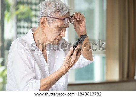 Asian senior woman with eye glasses,try to read messages,gaze at the small text on mobile phone,age related macular degeneration,blurred vision,poor eyesight problems,eye disease of the old elderly Royalty-Free Stock Photo #1840613782