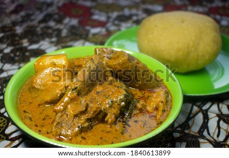 A Local Nigerian Dish of Eba or Garri and Palm Kernel Soup or Banga Soup served with assorted Meat on an Ankara Tablecloth. The soup looks quite alike with Ghanaian Groundnut soup, Delicious! Royalty-Free Stock Photo #1840613899