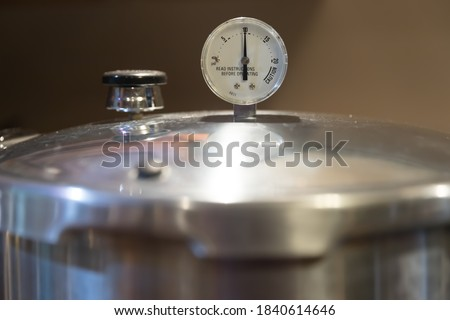A stainless steel pressure cooker lid with pressure gauge reading 10 pounds of pressure. Pressure canners are used to can vegetables from the garden. #1840614646