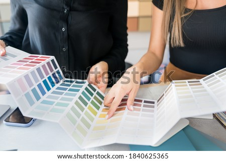 Close-up of two women choosing samples of wall paint. Interior designer consulting a client looking at a color swatch.  House renovation concept Royalty-Free Stock Photo #1840625365