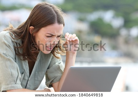 Stressed woman forcing sight wearing eyeglasees reading laptop outdoors  Royalty-Free Stock Photo #1840649818