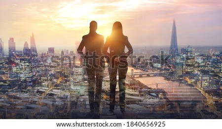 Two young woman looking at city of London at sunset. River Thames, embankment, business area of the City. London, UK