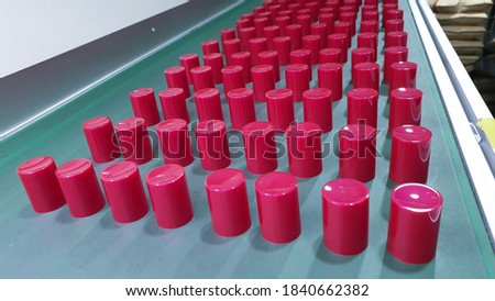 Dark red plastic bottle cap, photo of plastic injection parts on site of plastic factory, in plastics industry.