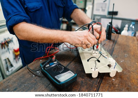 Marine electrical engineer officer in engine control room ECR. He works in workshop with electric equipment Royalty-Free Stock Photo #1840711771