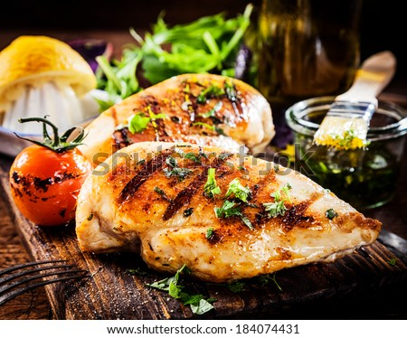 Marinated grilled healthy chicken breasts cooked on a summer BBQ and served with fresh herbs and lemon juice on a wooden board, close up view Royalty-Free Stock Photo #184074431