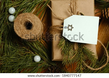 a Hanukkah gift is placed among the fir branches on a wooden table. Greeting card.  Royalty-Free Stock Photo #1840777147