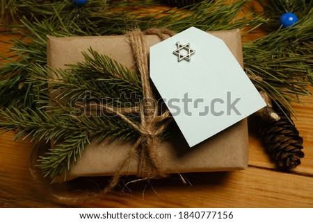 a Hanukkah gift is placed among the fir branches on a wooden table. Greeting card.