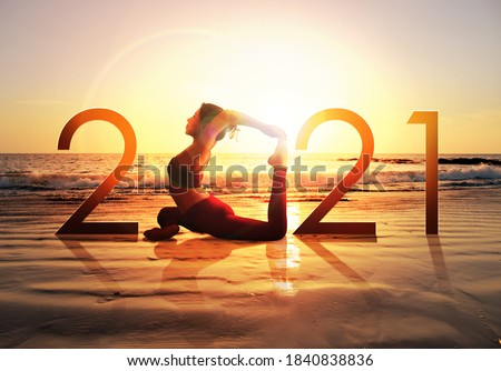 Happy new year card 2021. Silhouette of healthy girl doing Yoga One Legged Pigeon pose on tropical beach with sunset sky background, woman practicing yoga as a part of the Number 2021 sign. #1840838836