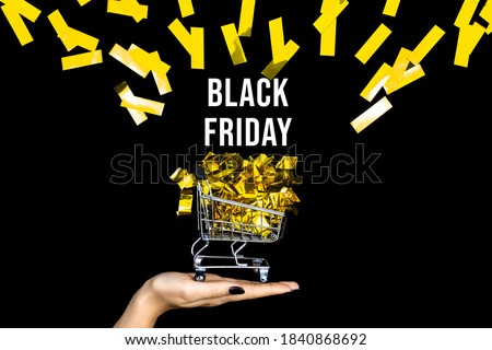 Little shopping cart with golden confetti. Trolley for clothes, products, gifts on background canvas. Black friday sale concept. Seasonal discount. Hot low prices. Best deal offer to buy cheap goods.