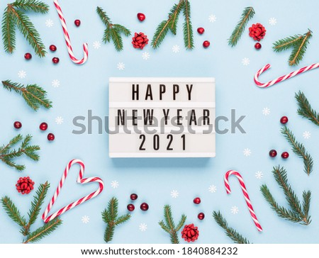 Christmas winter New Year composition. Happy New Year 2021 text on lightbox, Xmas candy canes, Fir tree branches, pastel blue background. Flat lay, top view, copy space. Holiday card mockup template.