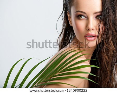Young beautiful woman with healthy skin of face and palm leaves. Closeup fresh face of an attractive caucasian girl with green plants. Model with bright brown eye makeup. Skin care concept.  Royalty-Free Stock Photo #1840900222