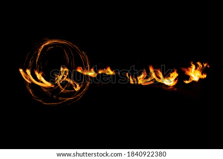 Orange fire pattern on black background. Dancing flame. Night fire show. Abstract flaming rotation trails. Long exposure.