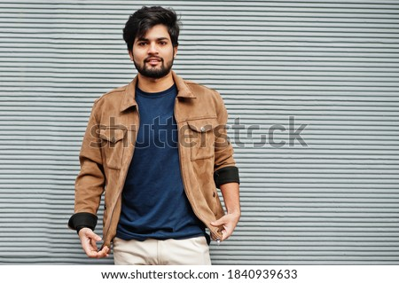Stylish casual indian man wear blue t-shirt and brown jacket posing against grey wall. Royalty-Free Stock Photo #1840939633