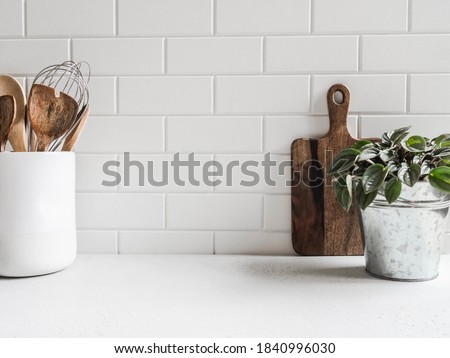 Stylish white kitchen background with kitchen utensils and green houseplant standing on white countertop, copy space for text, front view Royalty-Free Stock Photo #1840996030