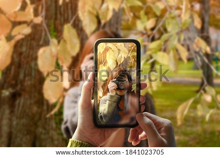 Taking Photo via Smartphone. Young Person Using Mobile Phone to Taking a Photograph for Friend in Outdoor Park.Model on Screen with Digital Camera do the same. Front View