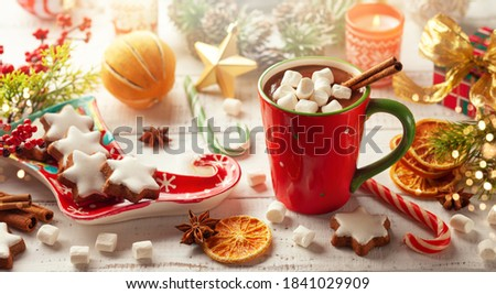 Concept Christmas homemade food and drink. Hot chocolate with marshmallows and cinnamon in red cup, Christmas cookies, winter spices and festive decor on wooden table. #1841029909