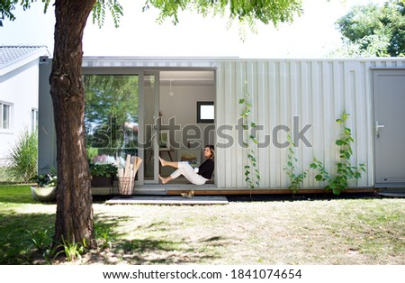 Mature woman working in home office in container house in backyard, resting. Royalty-Free Stock Photo #1841074654