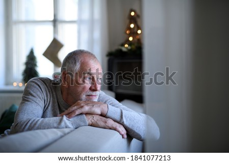 Lonely senior man sitting on sofa indoors at Christmas, solitude concept. #1841077213