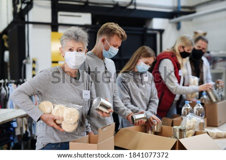 Group of volunteers in community charity donation center, food bank and coronavirus concept. Royalty-Free Stock Photo #1841077372