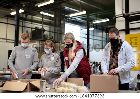 Group of volunteers in community charity donation center, food bank and coronavirus concept. Royalty-Free Stock Photo #1841077393