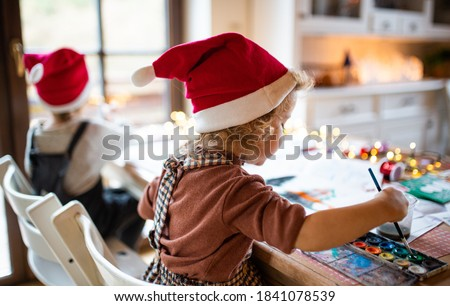 Rear view of small girl and boy indoors at home at Christmas, painting pictures.