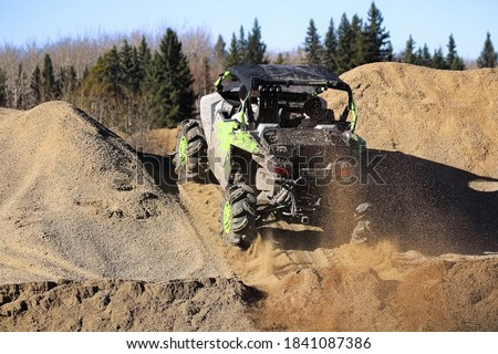 A side-by-side ripping up dirt as it goes up a gravel hill Royalty-Free Stock Photo #1841087386
