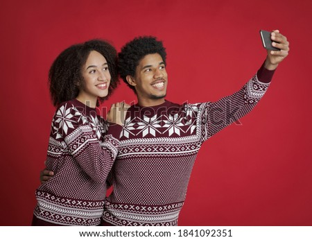 Guy and lady in identical New Year outfits happily pose for selfie. Smiling young african american couple watching in smartphone, make photo for Christmas card, isolated on red background, studio shot