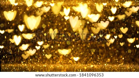 Christmas Gold glowing Background. Golden Holiday Abstract Glitter Defocused Backdrop With Blinking Stars and hearts. Gold Bokeh on black background. Festive defocused elegant border Royalty-Free Stock Photo #1841096353