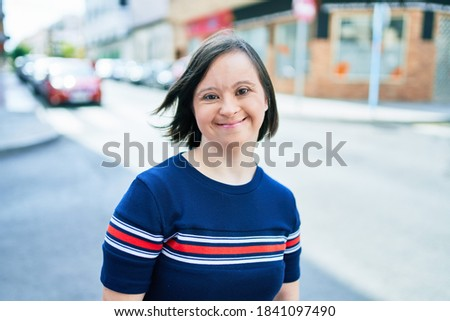 Beautiful brunette woman with down syndrome at the town on a sunny day Royalty-Free Stock Photo #1841097490